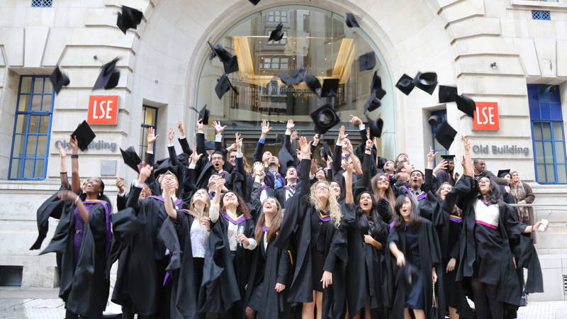 LSE Graduation students throwing mortar boards in the air on steps of the Old Building, Houghton Street