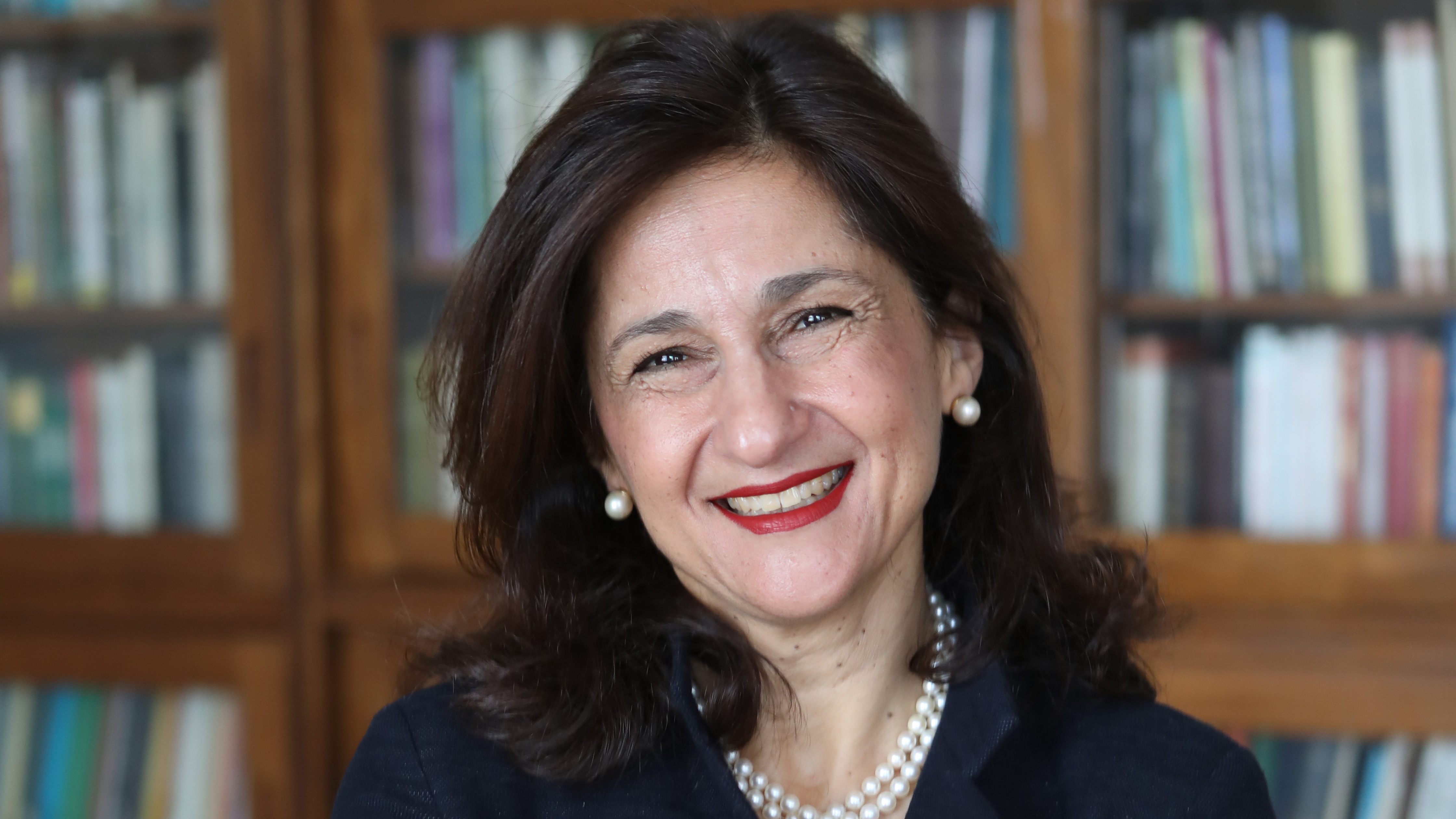Minouche Shafik smiling in front of a bookcase