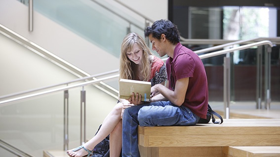 Two students looking at a book in the NAB atrium