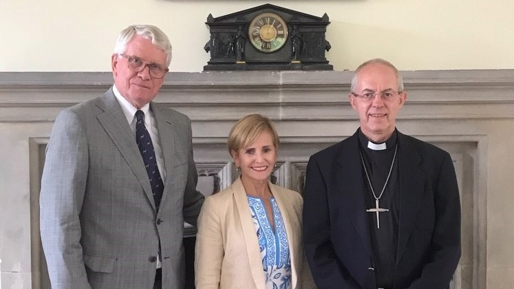 Dave and Kitty Beecken standing in front of a mantelpiece with Archbishop of Canterbury, Justin Welby. Left to right is Dave Beecken, Kitty Beecken and Justin Welby.