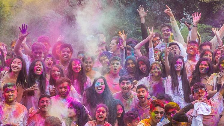 Hindu students celebrating Holi throwing bright paints in the air in celebration in the park.