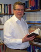 Professor Kevin Featherstone Head of the European Institute holding a book in the library