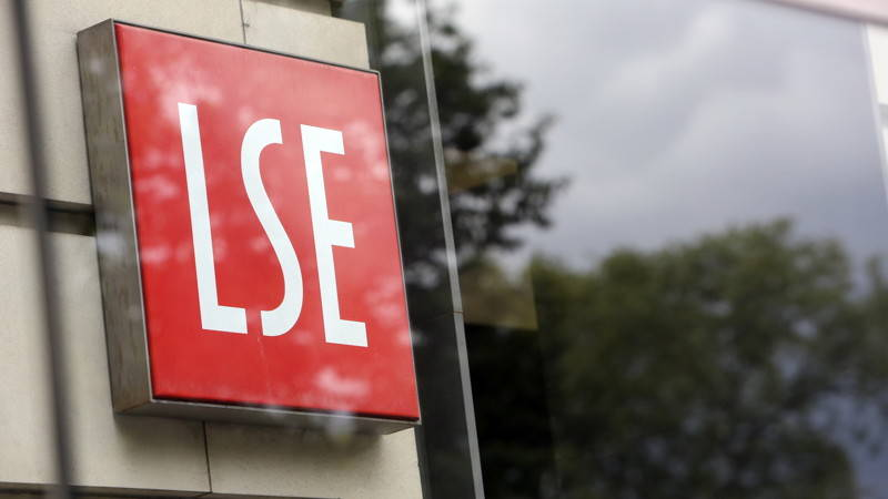 Red LSE logo on wall outside with greenery in the background