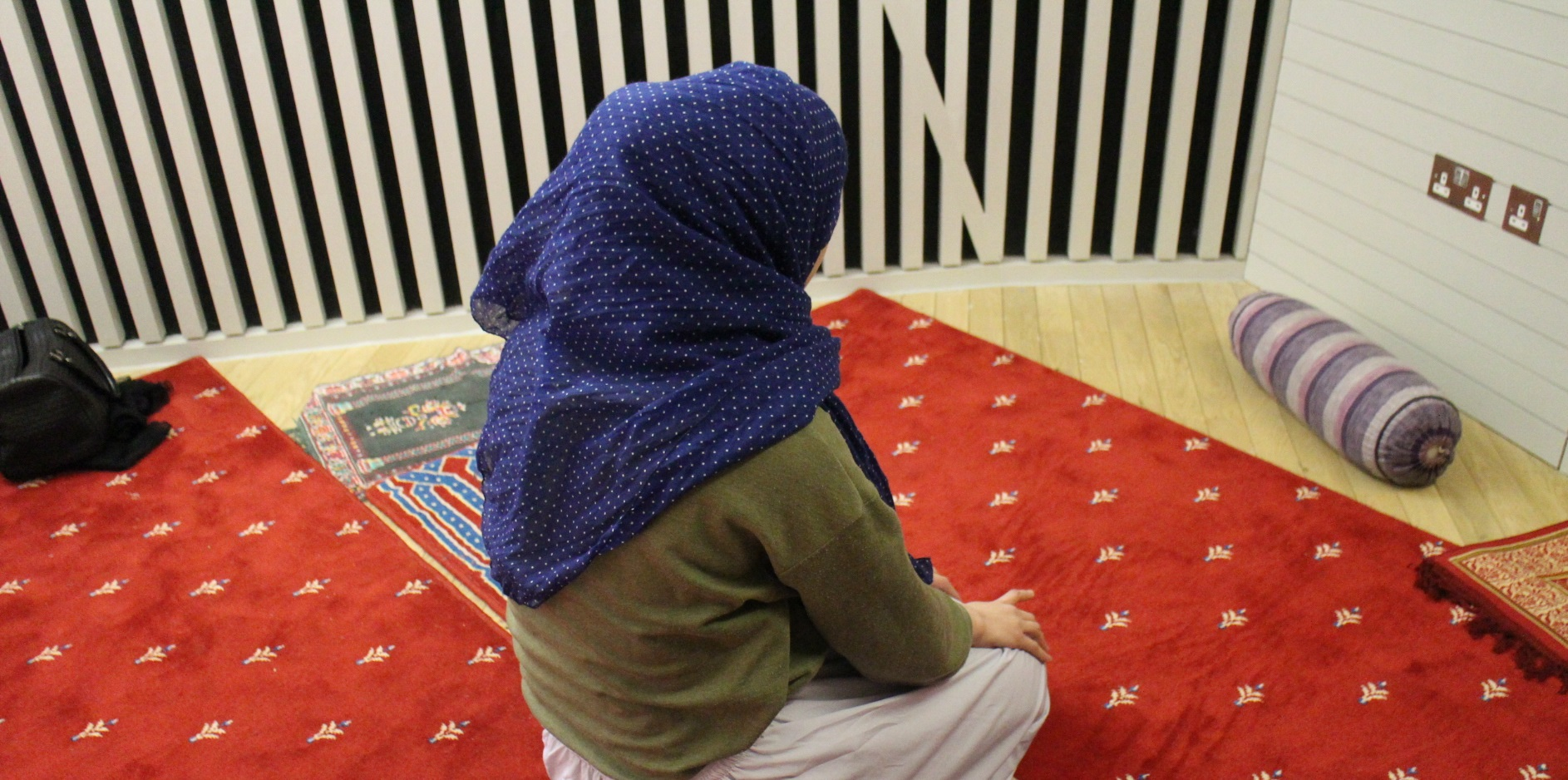 Muslim woman praying kneeling on the floor in the Faith Centre Islamic Prayer Room