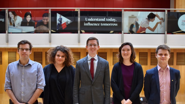 Faith Centre team members smartly dressed in atrium of LSE New Academic Building. Left to Right Daniel, Eliana, James, Angharad, Cameron.