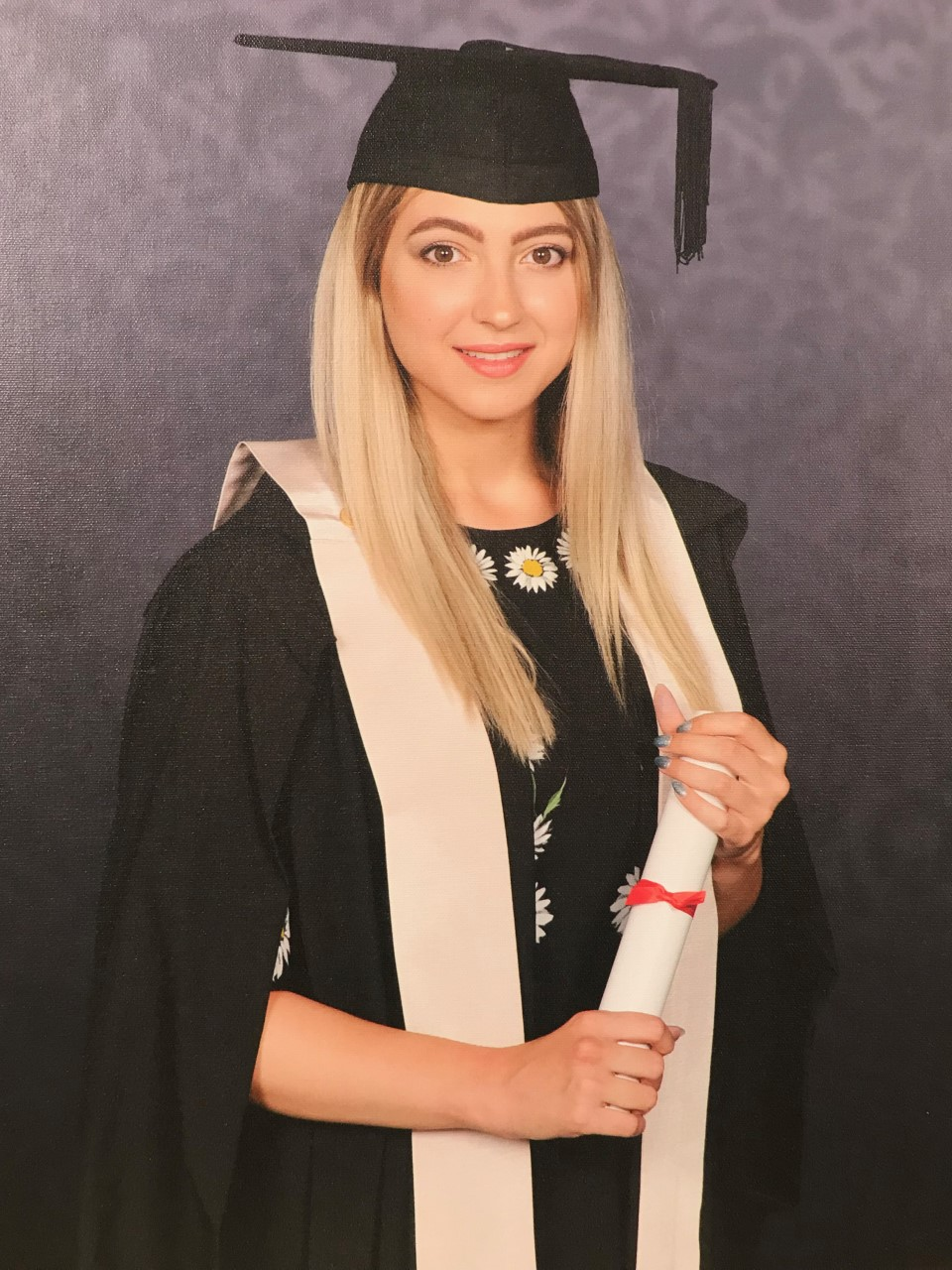 Xenia with graduation gown in front of grey background