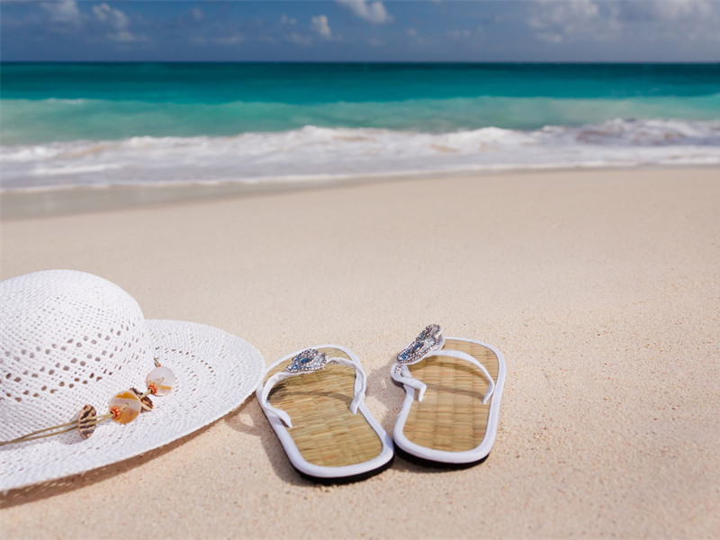 Hat and sandals on a beach