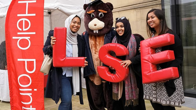 students at the LSE help point with a person dressed as a beaver
