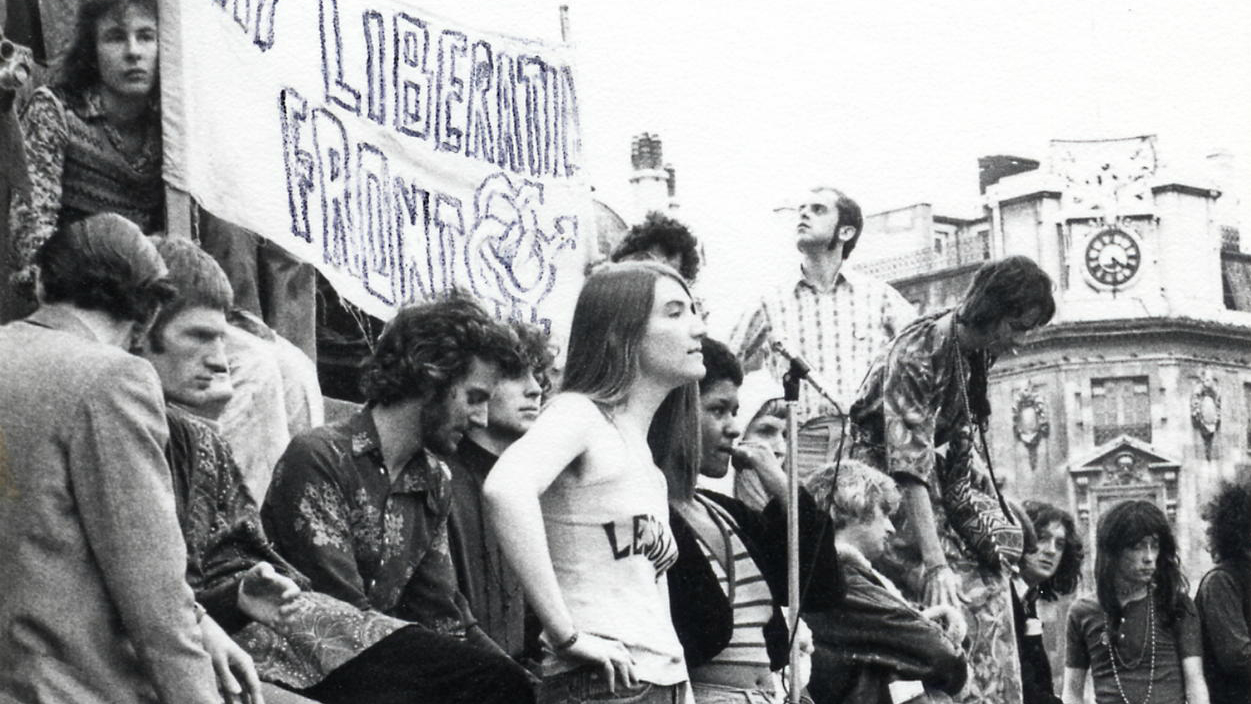 A 1972 demonstration, with people gathered around a Gay Liberation Front banner