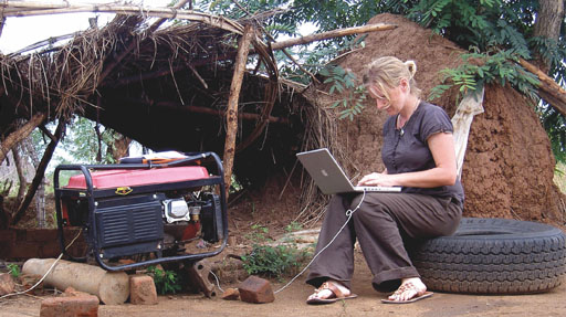 Woman sitting on a tyre works on a laptop in a makeshift camp
