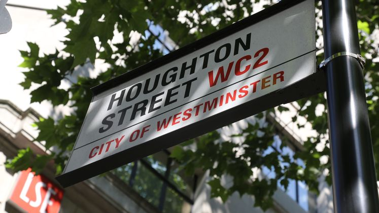 A sign saying Houghton Street beneath trees on a sunny day