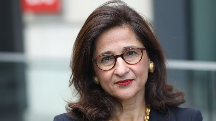 Minouche Shafik stands in front of the Old Building and looks at the camera