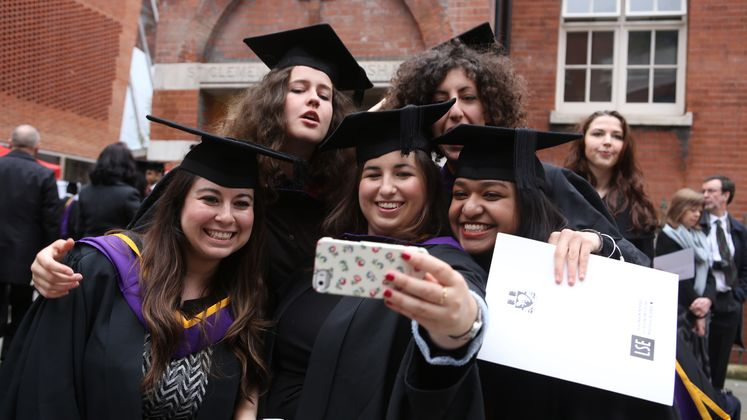 Graduating students in academic robes group together for a selfie