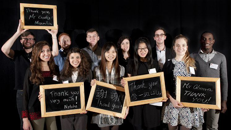 Students holding up blackboards with writing